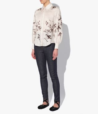 The Alexis Shirt in ivory has a pointed collar, blouson sleeves and a curved hem.