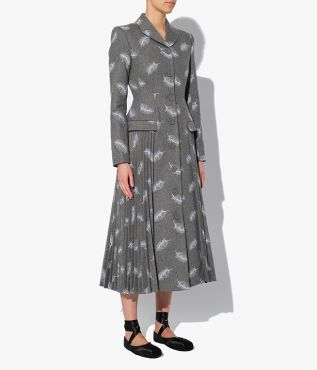 The Calla Coat features a lapel collar and structured shoulders as well as a nipped in waist and pleated panels at the A-line skirt.