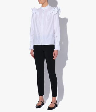 white cotton poplin shirt with a stand collar, trimmed with feminine ruffles at the shoulders and cuffs.