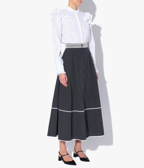 The Mervyn Skirt in navy is detailed with tiny white polka dots.