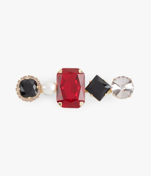 Brooch showcasing a line-up of contrasting red and black crystals, and a faux pearl.